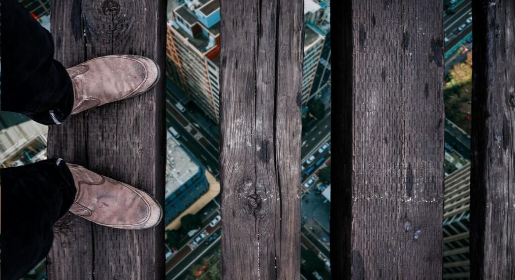 Imagem ilustrativa de risco: homem sobre madeiras em cruzamento